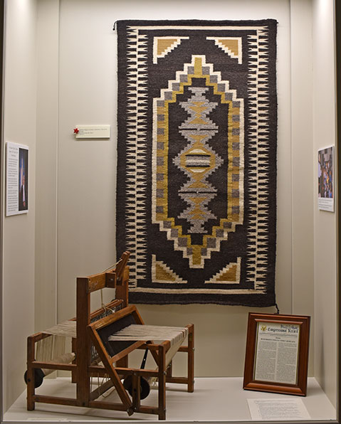 display case featuring a earth-toned weaving by eppie archuleta as well as a small table loom