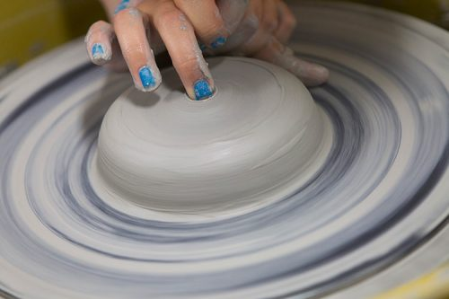 student at a ceramic spinning wheel