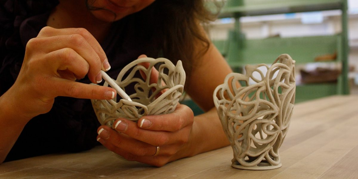 putting the finishing touches on a piece of pottery