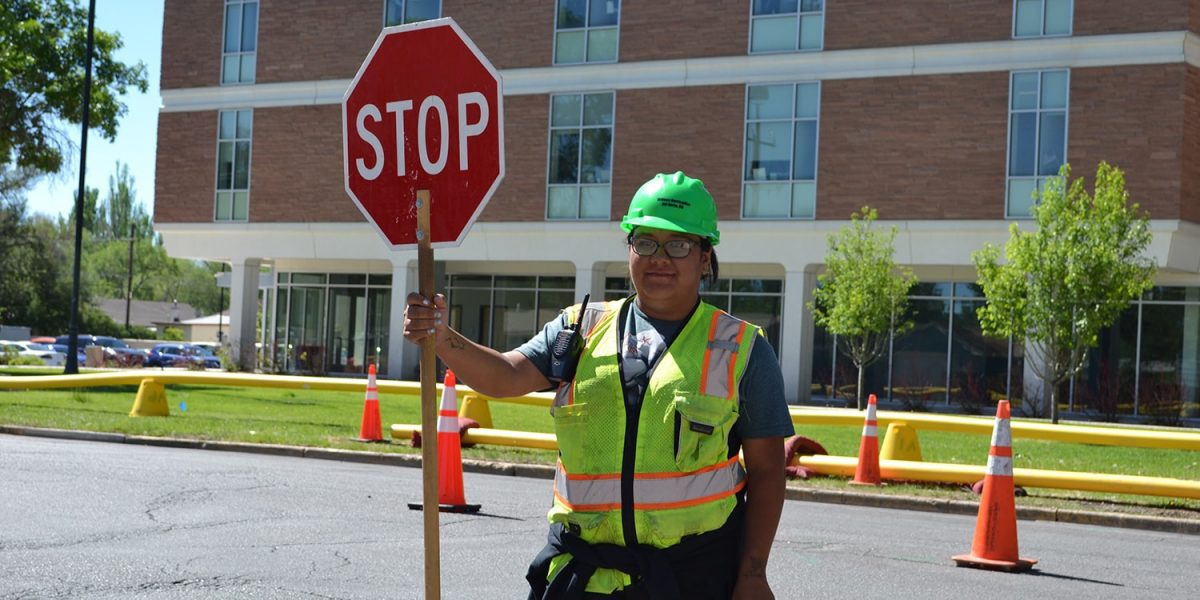 student holding a stop sign in a safety vest