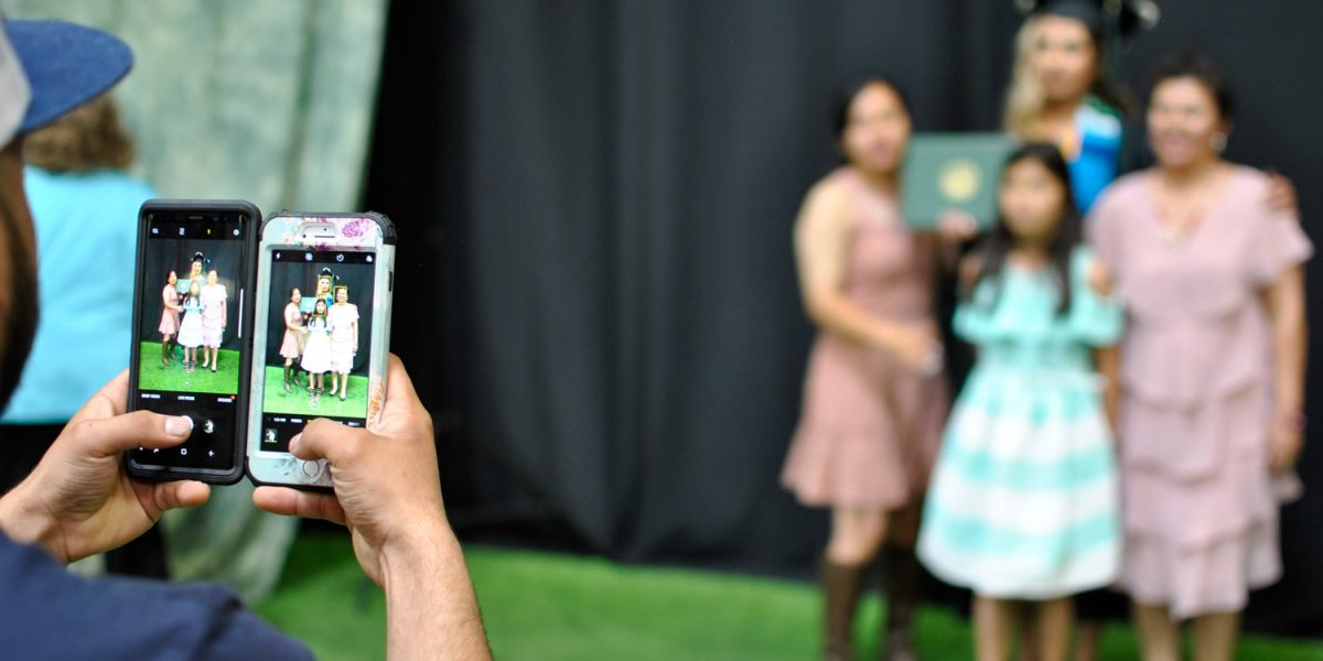 taking a picture of graduate and her family using two cell phones