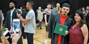 Adams State Graduate getting photo taken with cell phone