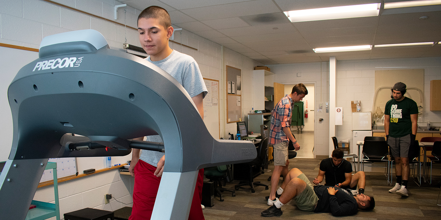 male student on treadmill students in background testing fitness