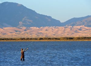 Fisherman in knee deep water casting with Great Sand Dunes in background