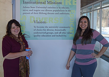 two students next to a poster of ASU's Vision and Mission Statements: Adams State University's mission is to educate, serve, and inspire our diverse populations in the pursuit of their lifelong dreams and ambitions. Vision: To become the university of community of choice for diverse, historically underserved groups, and all who value quality education and inclusivity.