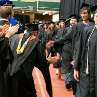 graduating students get high fives from professors after commencement