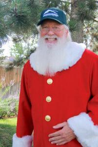 Man dressed as Santa with Adams State Hat on.