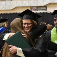 graduate hugs family member at Adams State Fall 2019 Commencement