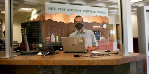 One Stop Student Services employee in front of laptop wearing mask