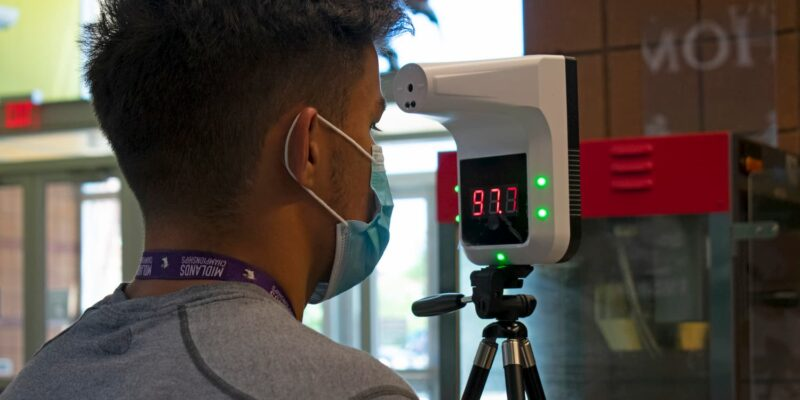Student gets their temperature check, wireless thermometer reads 97.7